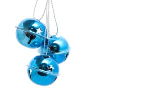 Pretty blue Jingle Bells Christmas decorations hanging against a white background with copyspace for your seasonal message